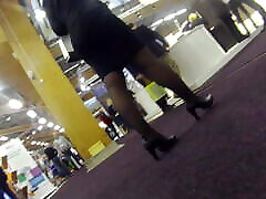 Candid office mature in black pantyhose and heels in a expo