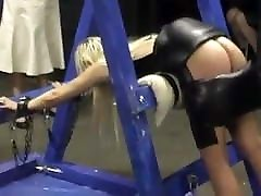 Women in leather skirt caning