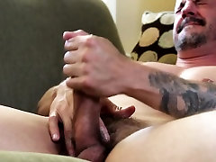 Beefy hunk strokes cock