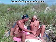 A couple of nudism lovers hardly pairing off on the sand