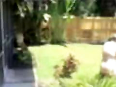 White sanny leoei Pounds Black Cub In BackYard