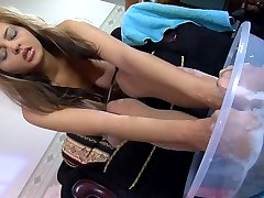 Pervy chick washes her pantyhose clad feet in soapy water using a sponge