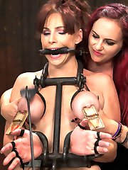 Bella Rossi returns for an epic Live Show at the hands of two sadistic bitches, Claire Adams and Mz Berlin. In the first scene, Bella and Claire play a little game of Marco - Polo done Device Bondage style. Claire and Bella are each blindfolded and Claire turns round in circles to give Bella the advantage then advances with the cattle prod. Since Bella is blindfolded she has no idea where and when she will be zapped! In scene two Bella is on her back like the cum hungry whore she is in wooden stocks. Her legs are bound to her elbows, frogged, then chained open so the bitch can't go anywhere. A zipper is painfully applied to her breasts and her feet are simultaneously caned by Mz Berlin and Claire. In the final position Bella is bound standing and bent over a custom metal apparatus. She is oiled up and her nice thick ass is paddled. Claire and Bella play a round robin between fucking her cunt and her mouth. Bella takes it like a champ, lifting her feet repeatedly off the floor and cumming hard.