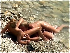 A tanned couple gets filmed fucking near the water