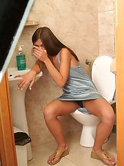 Horny brunette frigging her fanny in the toilet!