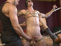 Logan Stone is a hot electrician who loves getting edged. He joins Jessie and Sebastian for a session in the Armory, where they waste no time in stripping Logan to his skivvies. The outline of Logan's cock bulges prominently as Sebastian ties Logan across the front of a four-post bed. Jessie gets a taste of Logan's meaty nipples and moves to his massive dick. With Logan blindfolded, Jessie holds out a fleshjack for Logan to fuck to completion, if only he could find it. Logan's cock chases the toy, finds it, and finally brings himself to cusp of orgasm -- right before Jessie tears it away. Sebastian repeats the torment with a vibrating sheath, bringing Logan to the edge and then tickling the stud at his most vulnerable moment. Jessie and Sebastian move Logan to the other side of the room and invert him. Logan has his tender cock sucked as he receive nipple suckers and a bit gag. Begging to cum through the gag, his tormentors plow his ass with a dildo before tying it off to his leg and making the stud fuck himself with it. Logan finally receives their permission to cum and blows a load all onto his face. Still in a daze from cumming, Logan is perfectly vulnerable for the last piece of torment. He twists and fights against his restraints as they tickle his body and polish his sensitive cock head.