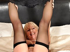 Mature blonde spreads her legs in bed