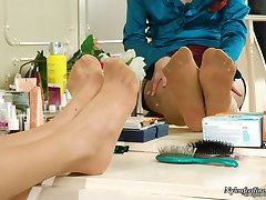 Cutie spying upon redhead gal flashing her nyloned feet in front of mirror