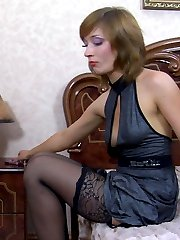Elegant lady takes off her cocktail dress and rolls down her lacy stockings