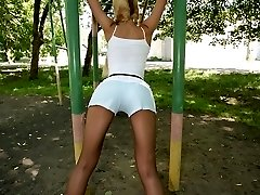 Blonde Emilias in stockings doing stretching exercises outdoors