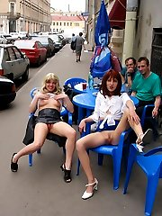 Two hot naughty models pose naked on city streets