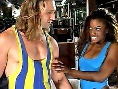 Watch a slutty ebony fox sucking a muscular guy's cock at the gym