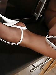 Awesome gal in glistening pantyhose displaying her ultra-cute feet in the kitchen