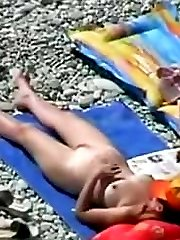 Absolutely naked babes taking sun baths on the beach were pictured up close