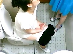Two cute Asian girls spotted on a restroom cam pissing