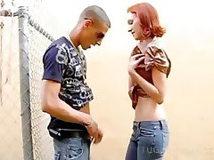 Topless redhead tugging hard cock thru a fence