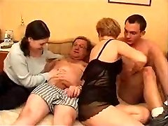 Mature couple with youthfull couple in bed