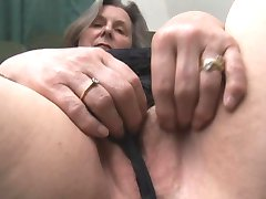 Busty granny in stockings shows off plump cameltoe and hairy puss