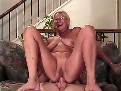 Mature blonde with glasses inhales a cock