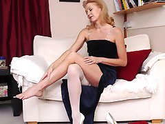 Hot blonde Milf Magdalena takes off her sexy white stocking and slowly puts it back on again in her matching stilettos