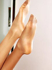 Lewd gal dangling her open toe shoes before slipping into her shiny tights