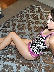 Brunette sweetheart Nicole B. is lying on the bed in her sexy outfit, showing only small tits