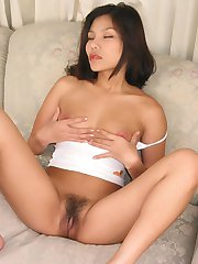 Pretty Asian model pleasuring her thick bush covered slit with a huge rubber dildo