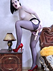 Sultry raven-head wears black suspender tights and red pumps for a toy fuck