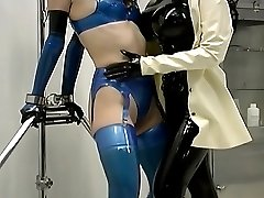 Sexy slave in blue latex lingerie gets her nipples licked by a beautiful medical dominatrix