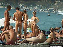Hot parade of tanned nude bodies filmed on a beach