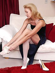 Hot blonde Milf Magdalena takes off her sexy white stocking and slowly puts it back on again in...