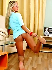 Blonde smashing looking gal eagerly fitting on bracelet on her nyloned feet