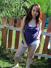 Busty redhair chick Alisyn C has great fun showing her big tits and ass outside