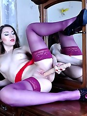 Upskirt babe in purple nylons with a red girdle finds a toy for her toy box