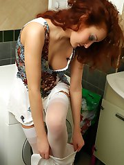 Red-haired cutie putting on white nylons and garter after taking a shower