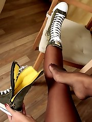Frisky girl in suntan reinforced toe hose having fun playing with a banana