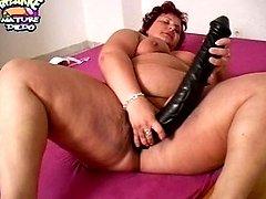 plowing her mature cunt with a huge dildo