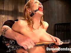 Rain is back, and hotter than ever. She is stood up and locked into a rigid device to prevent...