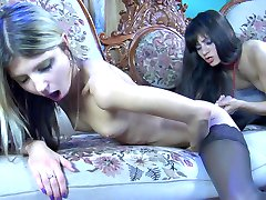 Two lesbian dolls launch into anal dildo play on the flowery vintage settee