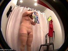 Yummy babe in stockings tries on a bikini under control