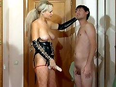 Kinky blonde mistress in leather gear plugs her subs mouth and bung hole