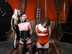 Mistress Erzsebet punishes two hot slaves by kneading their tits and making them kneel down