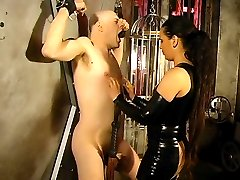 Mistress Asha bounds her slave to a wall and smacks his bare bottom crimson red with her whip