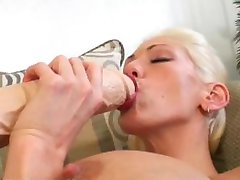 Busty blonde filling her shaved pussy with a long brutal dildo