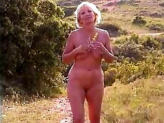 Chubby mature slut with saggy tits walks around outdoors