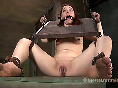 Slutty redhead gets her pierced pussy stretched out in this BDSM video